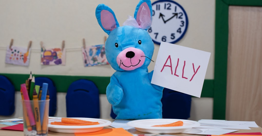 Ally the Bunny holding up a card with her name on it