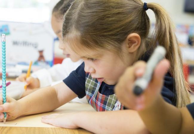 children writing in classroom