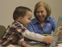 Primrose CEO Jo Kirchner happily shows a storybook to a young toddler