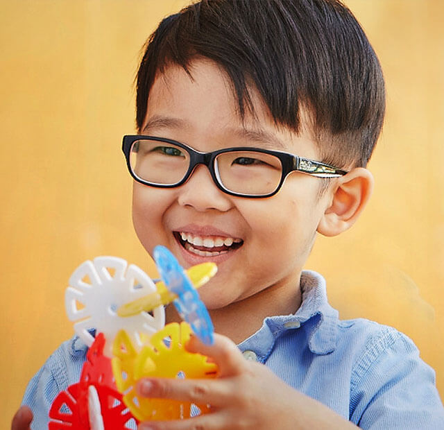 Young boy in glasses playing with a building activity set.